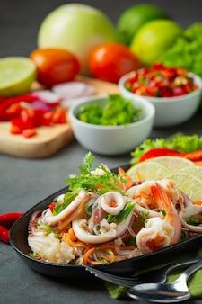 Salade de fruits de mer épicée avec des ingrédients de la cuisine thaïlandaise.