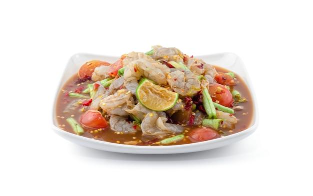 Salade de fruits de mer épicée à la thaïlandaise avec des crevettes sur le mur blanc.