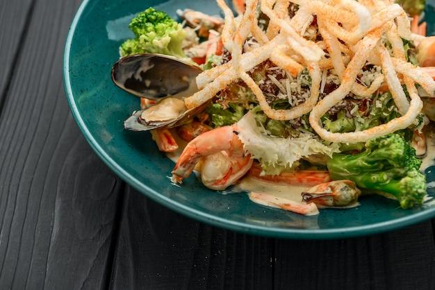 Salade de fruits de mer frais aux crevettes, moules et légumes sur fond noir