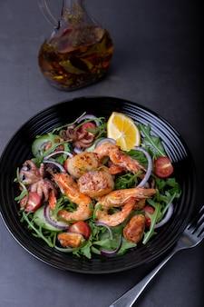 Salade de fruits de mer, roquette, tomates, concombres, oignon rouge et citron sur une assiette noire.