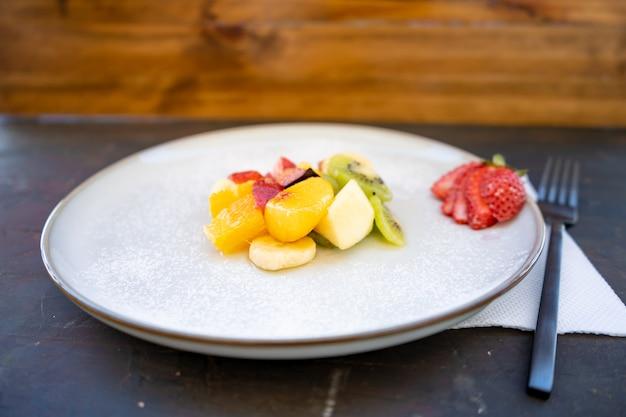 Salade de fruits naturels et sains à l'orange dans une assiette de présentation gastronomique sur une surface noire rustique.