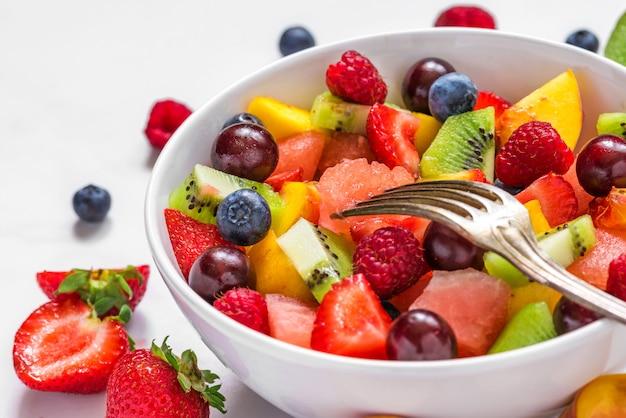 Salade de fruits avec pastèque, fraise, cerise, myrtille, kiwi, framboise et pêche dans un bol avec fourchette