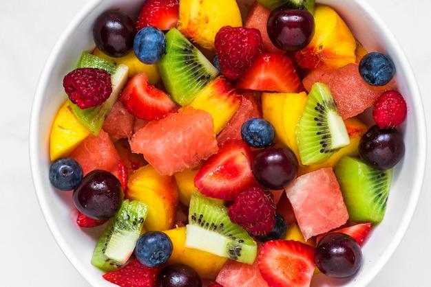 Salade de fruits avec pastèque, fraise, cerise, myrtille, kiwi, framboise et pêches dans un bol. nourriture végétalienne saine