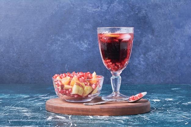 Salade de fruits avec une tasse de vin sur bleu.