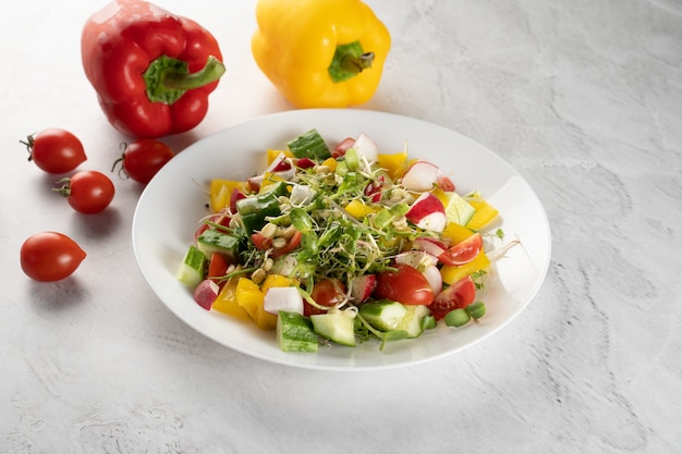 Salade de germes de blé, tomates, poivrons, radis, concombre, huile d'olive. salade de légumes sur plaque blanche sur fond gris.
