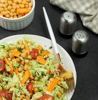 Salade grand angle avec pois chiches et salière et poivrière