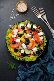 Salade grecque en assiette en céramique sur béton noir