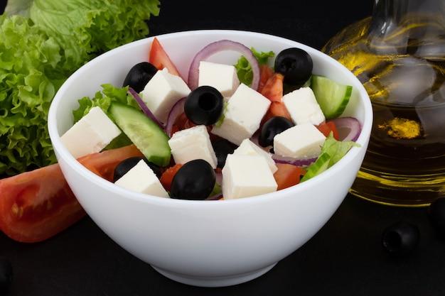Salade grecque aux légumes frais, fromage feta et olives noires sur fond sombre.