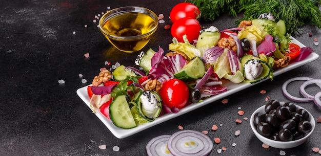 Salade grecque aux légumes frais, fromage feta et olives noires. salade saine aux tomates cerises, olives biologiques, concombre, laitue et épices