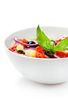 Salade grecque aux légumes, garnie de basilic.