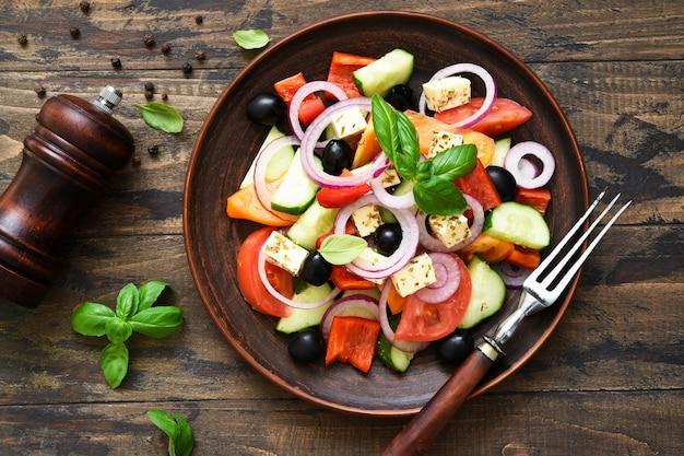 Salade grecque classique avec feta sur un fond en bois.