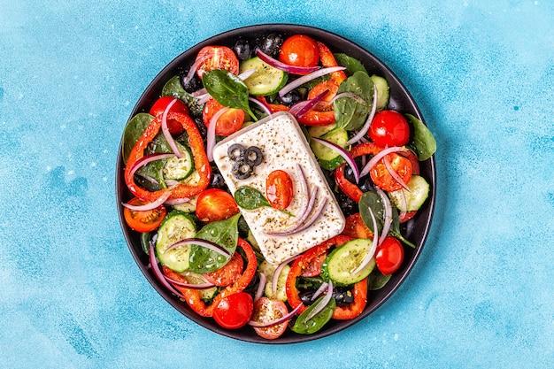Salade grecque de concombre frais, tomate, poivron, épinard, oignon rouge, fromage feta et olives