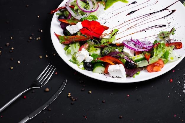 Salade grecque de concombre frais, tomate, poivron, laitue, oignon rouge, fromage feta et olives à l'huile d'olive.