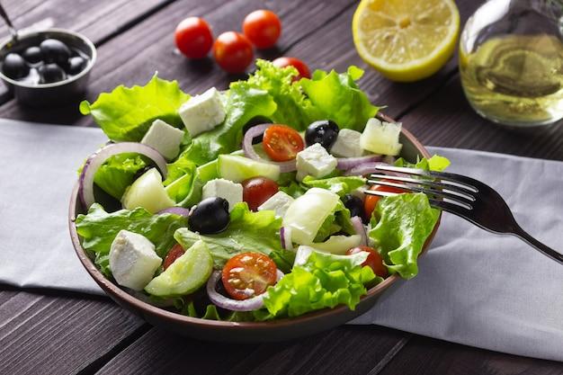 Salade grecque dans une assiette sur un fond en bois foncé. nourriture végétarienne saine.