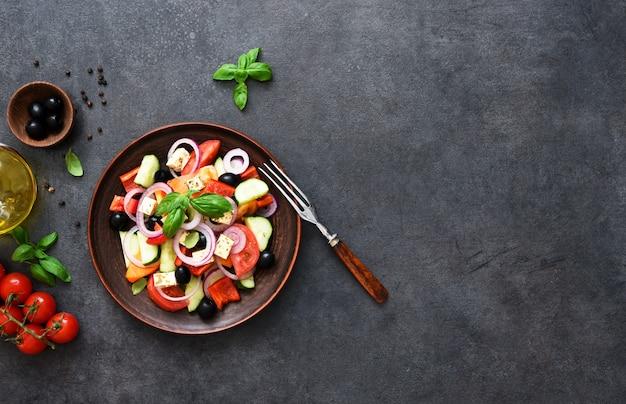 Salade grecque avec feta et olives sur fond de béton noir. vue d'en-haut.