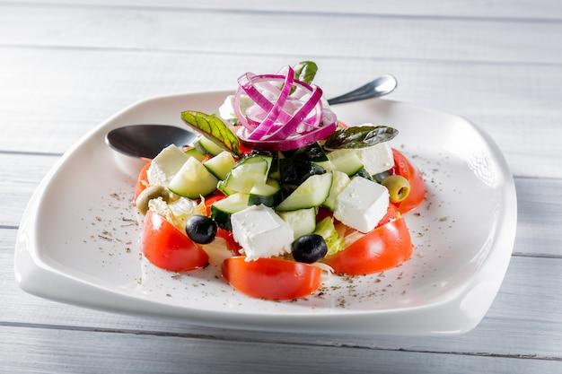 Salade grecque fraîche sur une assiette blanche avec oignons