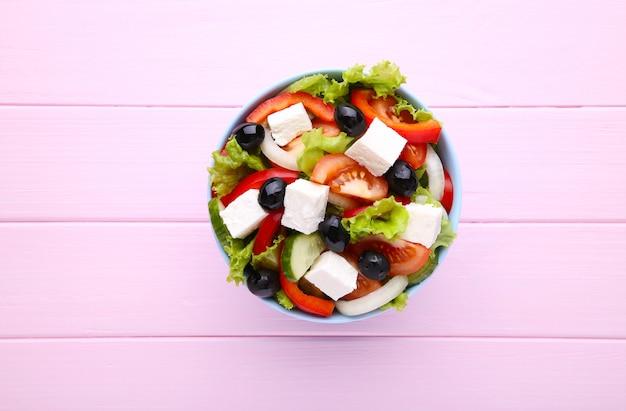 Salade grecque fraîche sur un bol sur un fond en bois rose