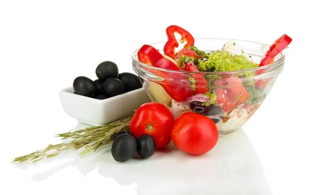 Salade grecque fraîche dans un bol en verre sur blanc