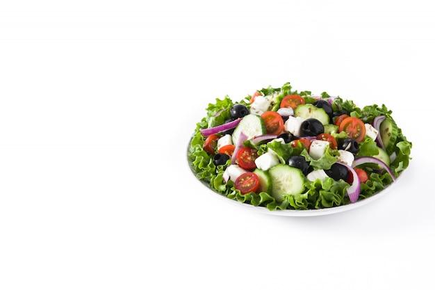 Salade grecque fraîche en plaque avec olive noire, tomate, fromage feta, concombre sur blanc.