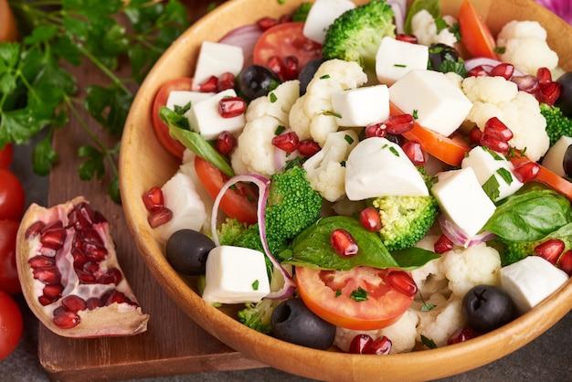 Salade grecque ou horiatiki avec de gros morceaux de tomates, concombres, oignons, fromage feta et olives dans un bol blanc vue de dessus isolée. salade du village avec mozzarella en dés, roquette, persil et huile d'olive
