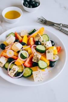 Salade grecque à l'huile d'olive sur marbre.