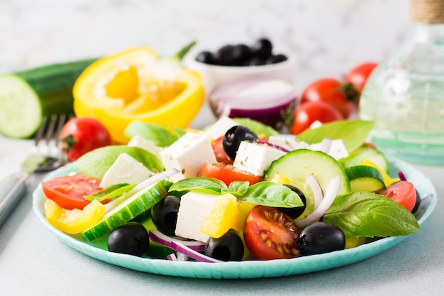 Salade grecque maison fraîche avec des feuilles de basilic sur une assiette et des ingrédients pour la cuisson sur la table
