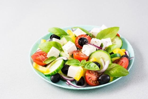 Salade grecque maison fraîche avec des feuilles de basilic sur une assiette sur la table