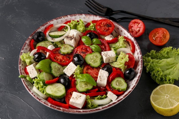 Salade grecque saine de laitue verte, tomate cerise, oignon, poivre, fromage feta, olives noires, basilic, concombres, avec de l'huile d'olive et du jus de citron, gros plan