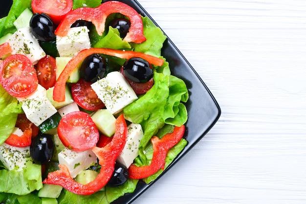 Salade grecque sur une table en bois blanc