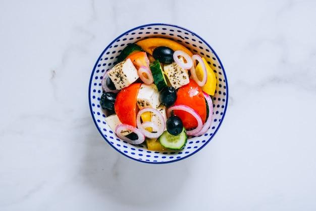 Salade grecque vue de dessus avec de l'huile d'olive sur marbre.