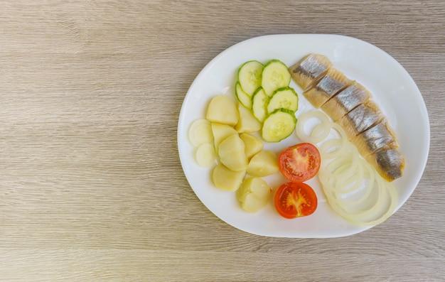 Salade de hareng aux légumes sur la vue de dessus de plaque blanche