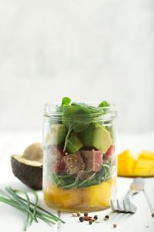 Salade hawaïenne poke au thon, avocat, mangue et légumes dans un pot avec fourchette et légumes