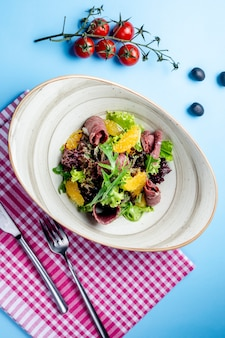 Salade d'herbes au jambon et tranches d'orange