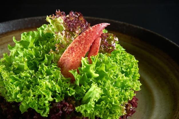 Salade de homard frais et diététique servie dans un bol. isolé sur fond noir. fruit de mer
