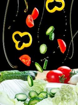 Salade d'ingrédients volants isolée sur un fond noir. salade flottant dans l'air au-dessus de la table. légumes laitue et huile d'olive