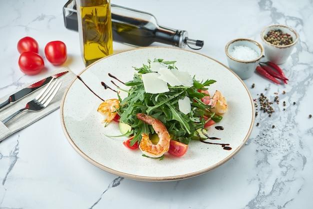 Salade italienne appétissante avec roquette, crevettes, avocat et parmesan dans une assiette sur une surface en marbre