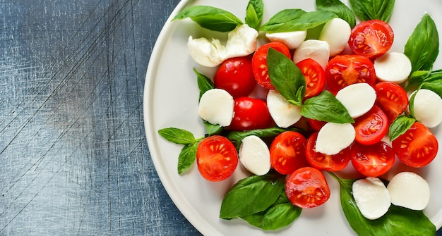 Salade italienne caprese: tomates rouges, mozzarella et basilic, cuisine italienne. déjeuner sain.