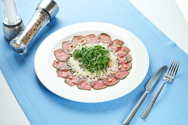 Salade italienne classique - boeuf vitello tonato avec roquette, parmesan et sauce aux truffes dans une assiette blanche sur une nappe bleue. gros plan, mise au point sélective