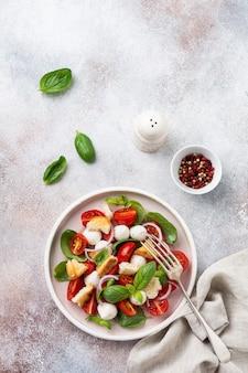 Salade italienne traditionnelle panzanella avec tomates cerises, fromage mozzarella, basilic et pain dans une assiette en céramique. vue de dessus.