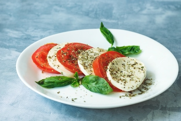 Salade italienne traditionnelle avec des tomates mûres fromage mozzarella avec des feuilles de basilic frais