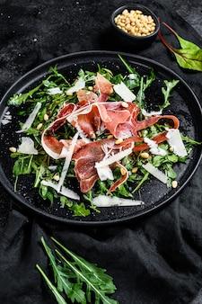 Salade de jambon serrano, jambon, roquette et parmesan. fond noir, vue de dessus.