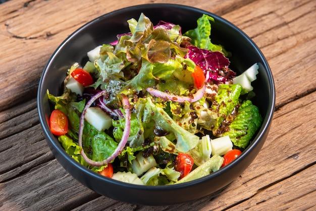 Salade japonaise dans un bol en céramique noire, plateau de table en bois.