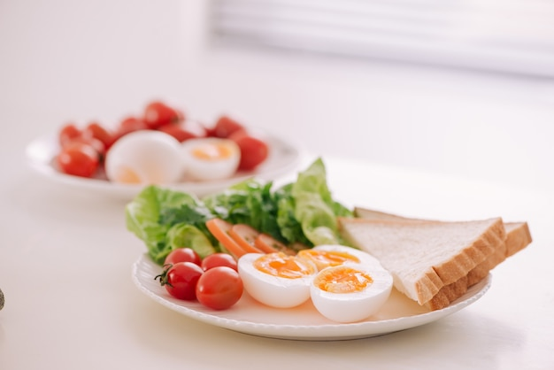 Salade de jardin fraîche avec œuf, avocat et tomate dans un plat en grès brun pour un déjeuner sain à faible teneur en calories.