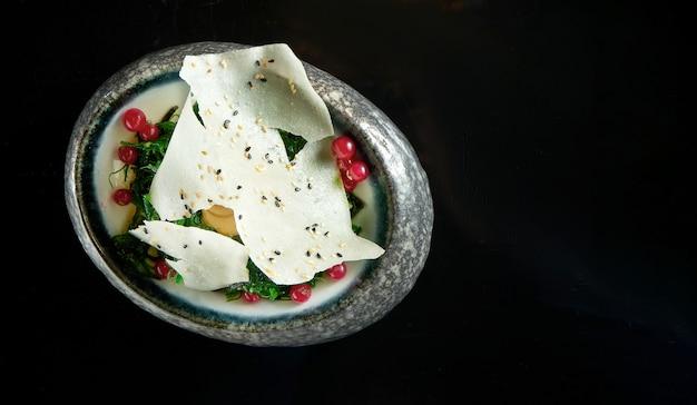 Salade de kaiso avec sauce aux arachides et chips de riz, servie dans un bol blanc. salade d'algues - wakame. isolé sur un tableau noir. nourriture de restaurant. cuisine japonaise