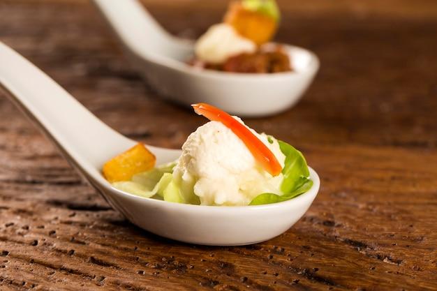 Salade de laitue bébé, tomates cerises, cœurs de palmier, sauce chou-fleur, manioc frit et chantilly salée dans une cuillère. goûtez la fingerfood de la gastronomie