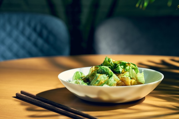 Salade de laitue chinoise à la sauce aux huîtres et à l'ail dans une assiette blanche