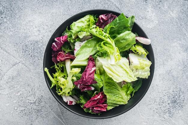 Salade de laitue frise, romaine et radicchio, sur fond gris, vue de dessus à plat