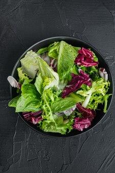 Salade de laitue frise, romaine et radicchio, sur fond noir, vue de dessus à plat