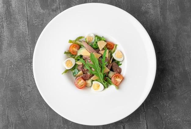 Salade de langue de boeuf et roquette. sur une grande assiette blanche. vue d'en-haut. fond de béton gris.