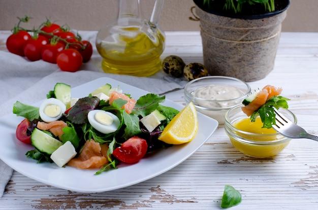 Salade de légumes en assiette blanche avec tomates cerises, sauce et huile d'olive